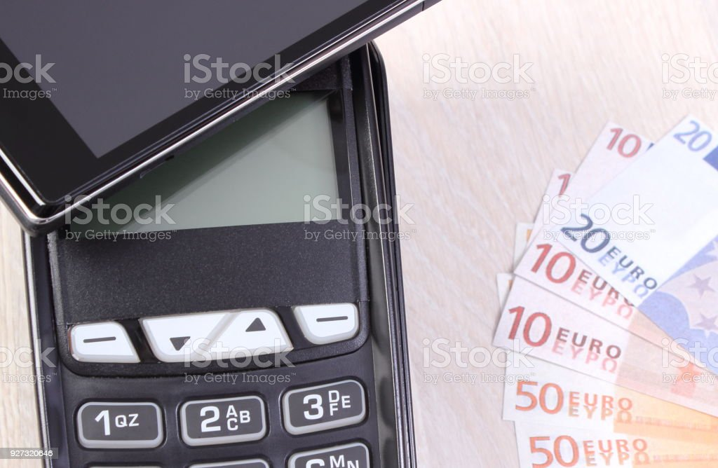 Payment terminal with mobile phone with NFC technology and currencies euro stock photo