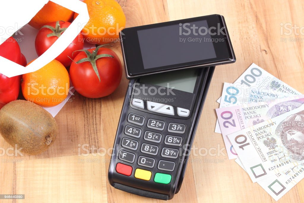 Payment terminal with mobile phone with NFC technology and polish currency, fruits and vegetables stock photo