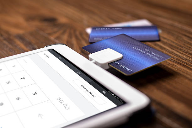 Payment with a Credit Card Chip Reader on a Tablet Credit card payment on a swipe or chip reader app on a tablet used by small or online businesses.  The electronic device is used as a modern cash register or for banking.  The image depics modern method of currency transactions for business. smart card stock pictures, royalty-free photos & images