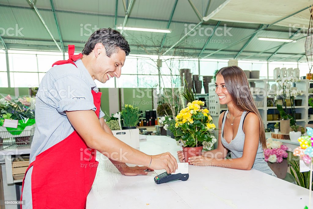 payment with smartphone at checkout in nursery retail store stock photo