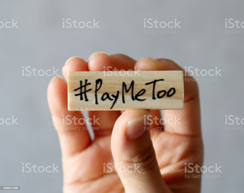 #PayMeToo movement concept. Hand holding a wooden block with #PayMeToo stock photo