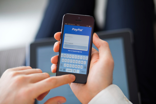 Moscow, Russia - February 20, 2014: Close-up man hands uses iPhone 5 with PayPal app. PayPal is an international e-commerce business allowing payments and money transfers to be made through the Internet.