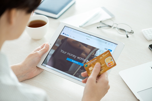 Kiev, Ukraine - June 27, 2014: Person with credit card in hand looking on a brand new Apple iPad Air with Paypal website on a screen. Paypal is the worldwide e-commerce business service allowing payments and money transfers via internet, founded in June, 1998.