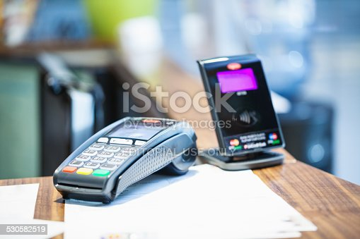Belgrade, Serbia - November 21, 2014: Credit card payment terminal with contactless payment (pay pass) device in background; selective focus, close up;
