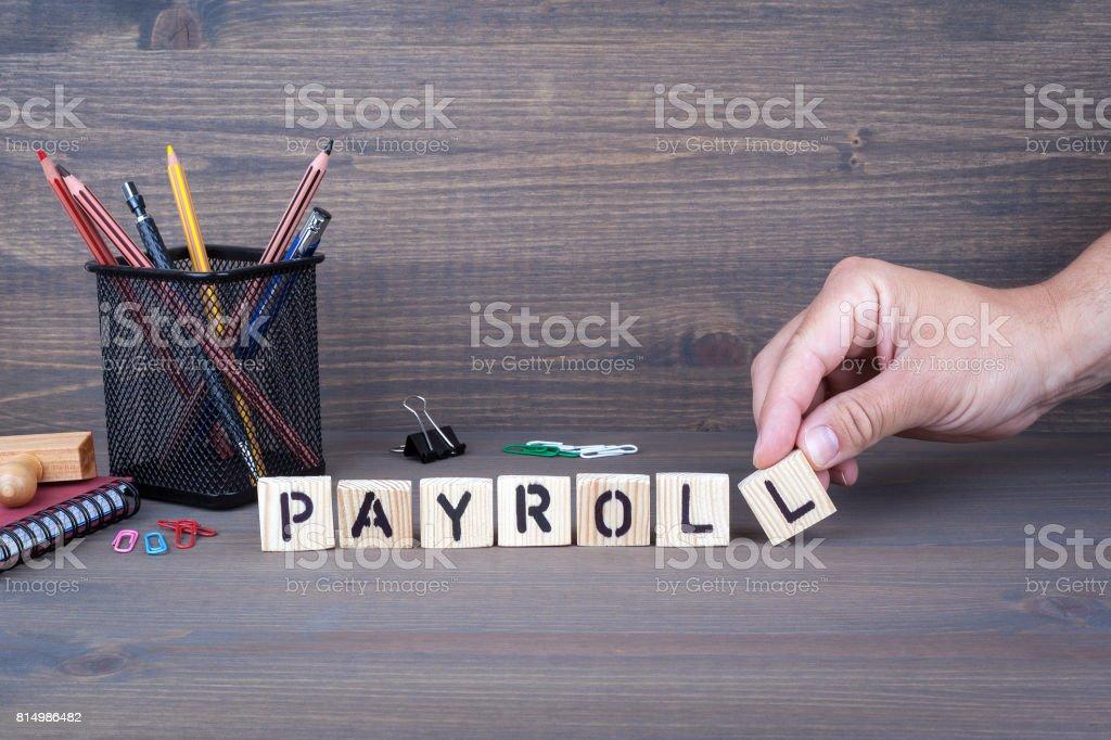 Lohn-und Gehaltsabrechnung. Holzbuchstaben auf dunklem Hintergrund Lizenzfreies stock-foto