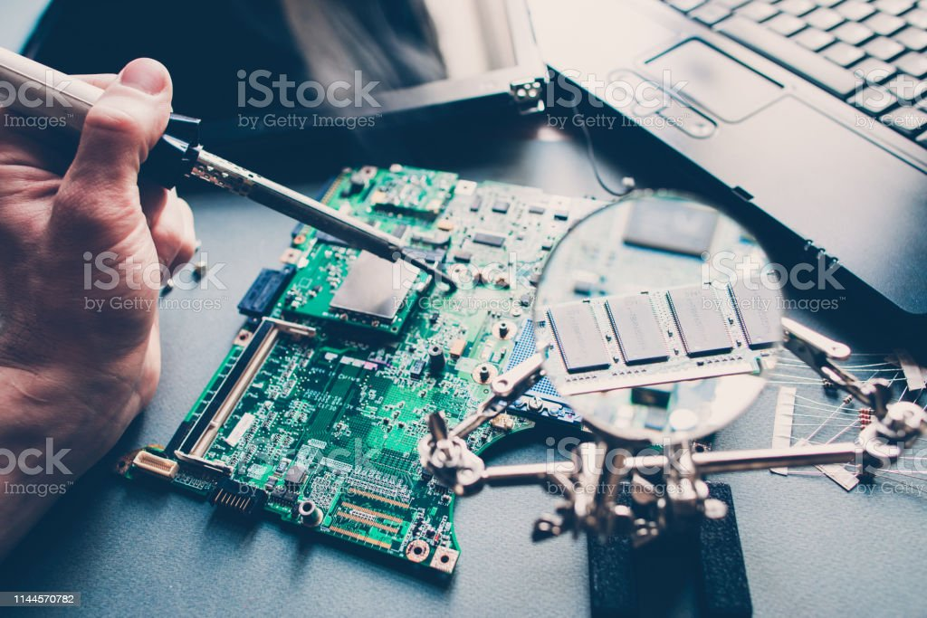 pcb layout repairing technician soldering laptop Technician repairing pcb layout with soldering iron. Broken disassembled laptop. Electronic components. Computer analysis. Abstract Stock Photo