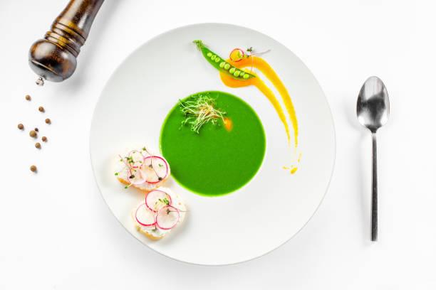 リム スープ皿にエンドウ豆のクリーム スープ - フランス料理 ストックフォトと画像