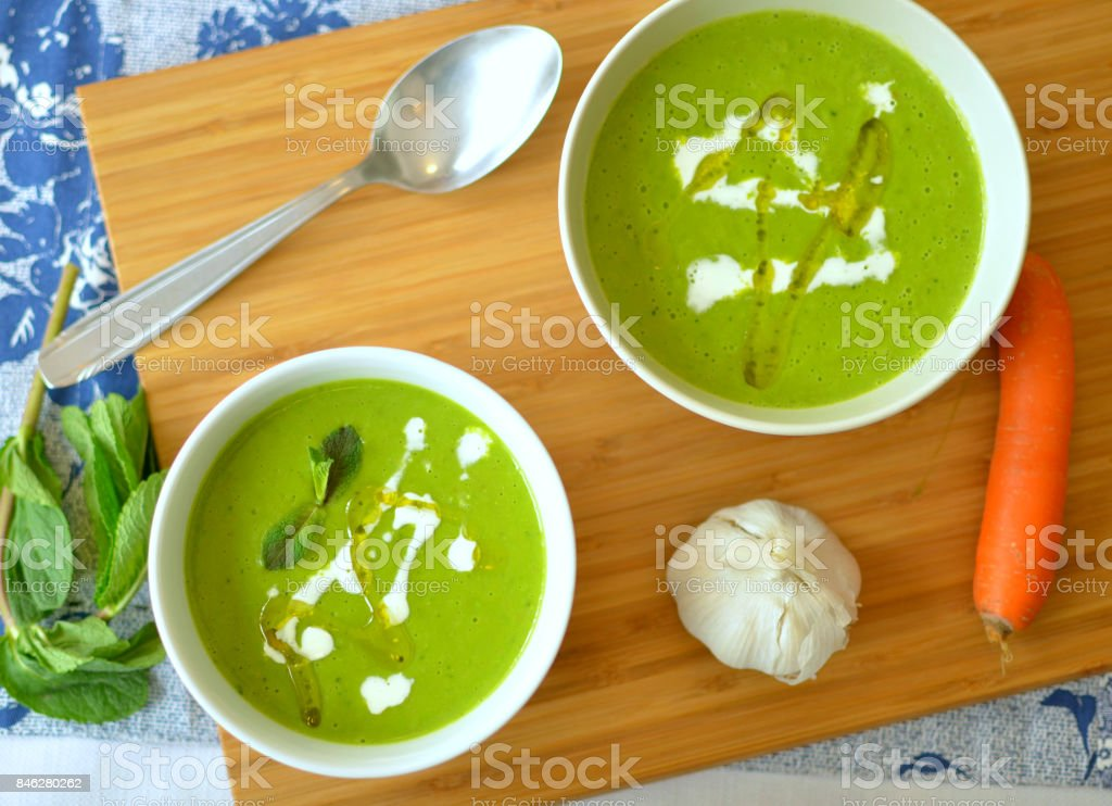 Pea, mint and carrot cream soup stock photo