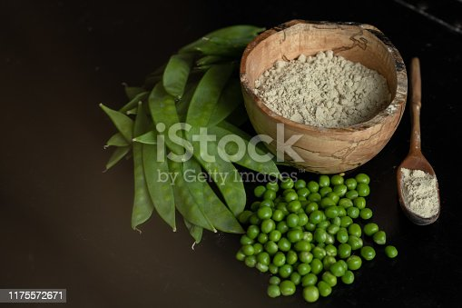 Pea protein powder is pictured in a wooden bowl, and in a wooden spoon from a side view. Next to them is a pile of snow peas and snap peas.