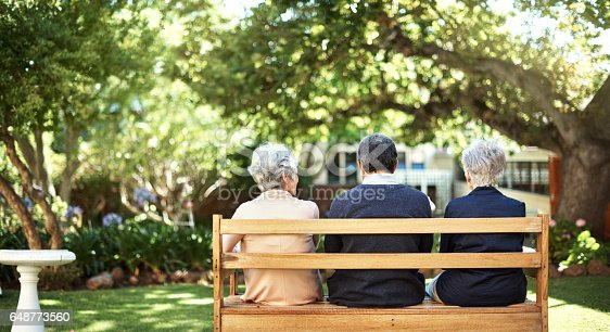 Rearview shot of a group of seniors sitting together on a bench out in the garden