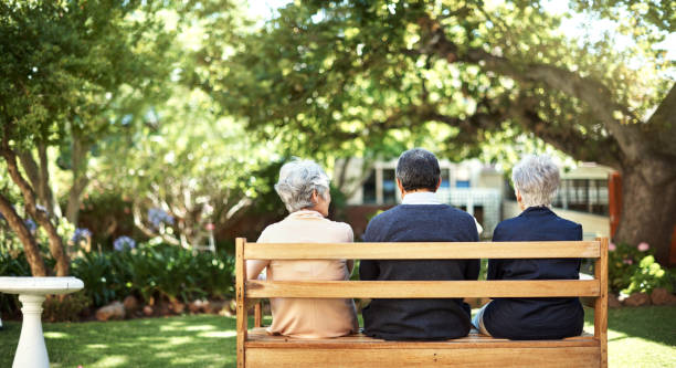 Peace and quite out in the gardens Rearview shot of a group of seniors sitting together on a bench out in the garden retirement community stock pictures, royalty-free photos & images