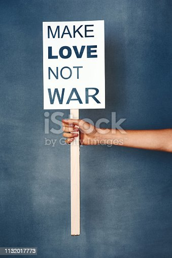 "Studio shot of an woman holding a sign that says ""make love not war"" against a blue background"