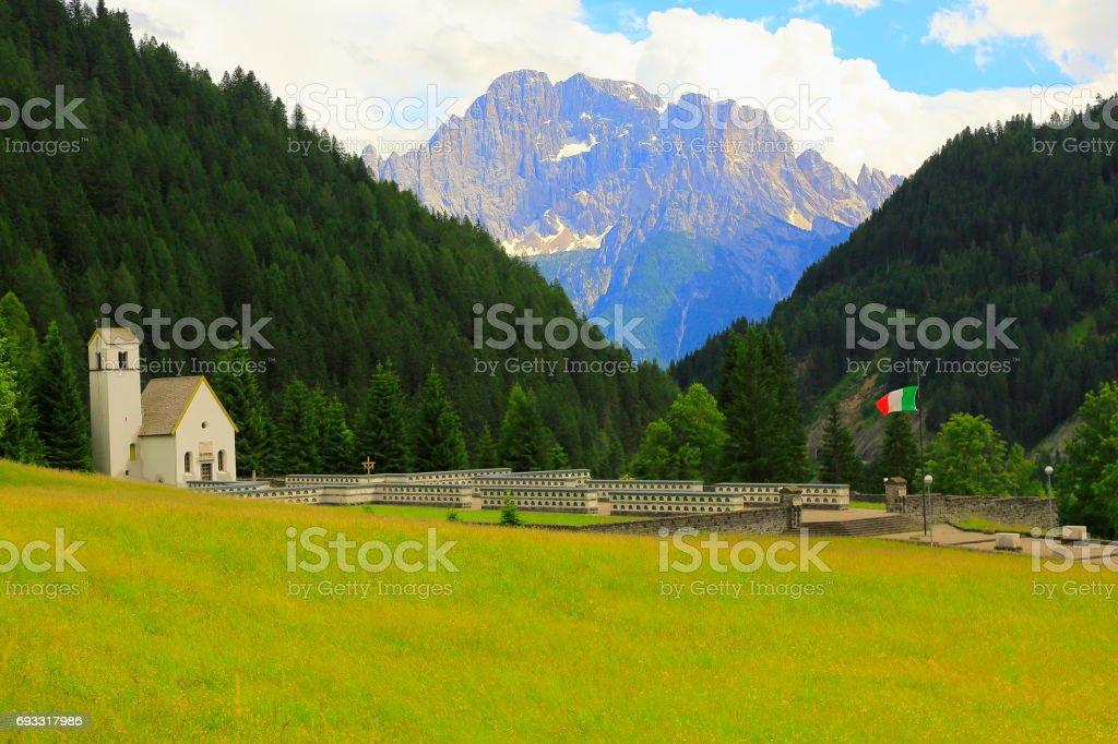 Peace: Italian World War I Memorial in Dolomites and Chapel with Italian Flag, under Majestic Mount Civetta stock photo