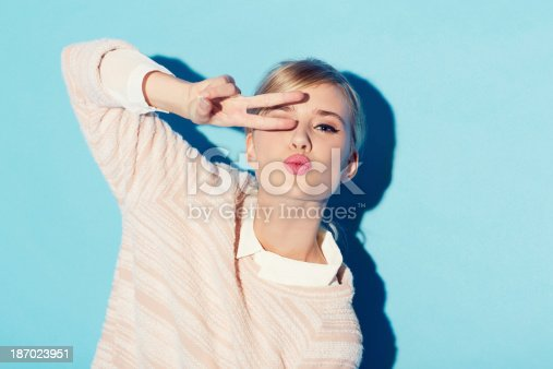 A gorgeous young woman covering her one eye with two fingers while standing in front of a blue background