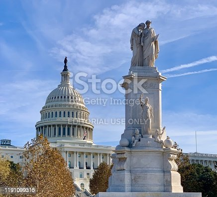 Washington, DC, United States - November 26, 2019: Peace Monument (Naval Monument) with dome of the United States Capitol in the background. The Peace Monument was erected from 1877-1878 to commemorate the naval deaths at sea during the American Civil War.