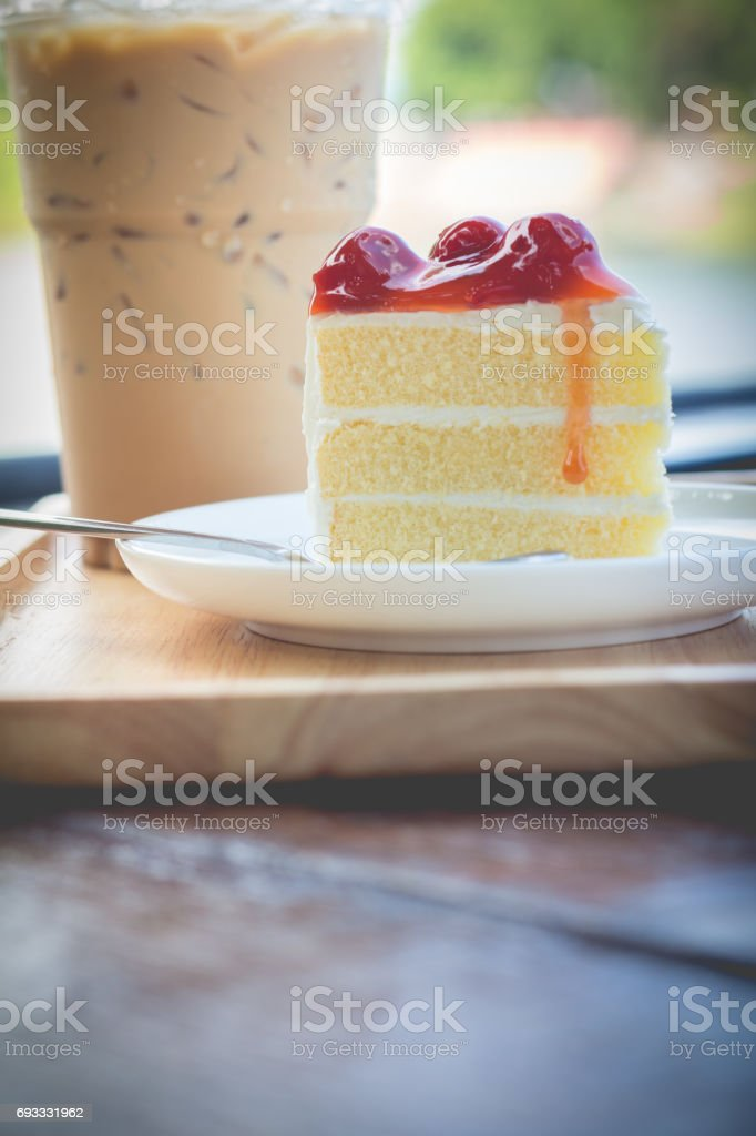 Peace of cherry cake serve with iced coffee. Cherry cake in cozy outdoor cafe. stock photo