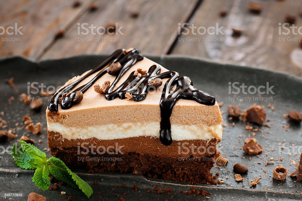 Peace of layered souffle dessert with chocolate sauce on black plate...