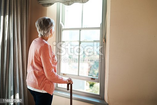 Shot of a senior woman with a cane looking thoughtfully out of a window at home