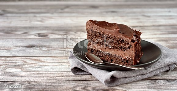 A peace of vegan chocolate davil cake on grey wooden background. Copy space