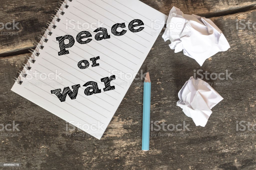 Peace or War text on a notebook with pen crumpled paper. stock photo