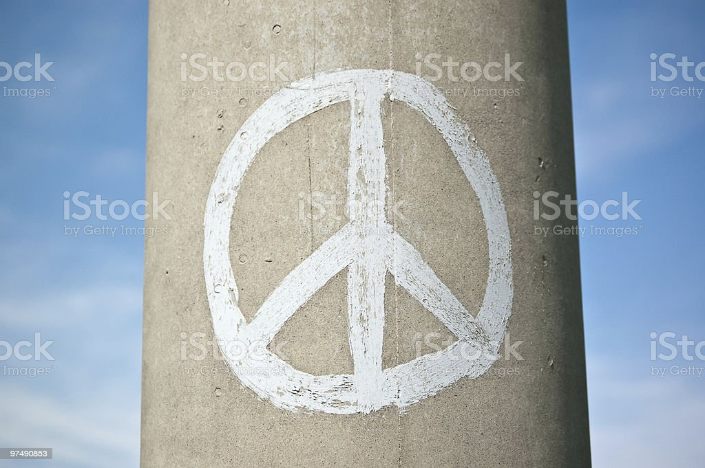 Peace Sign on a Concrete Pillar with Blue Sky royalty-free stock photo
