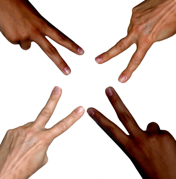 Peace signs made by four different skin color hands stock photo