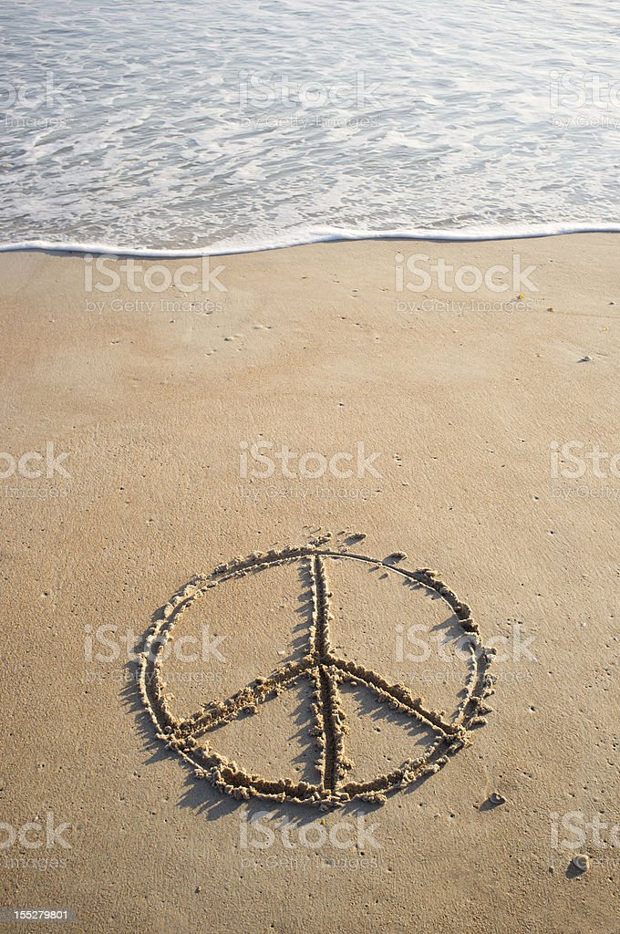 Peace symbol drawn in beach sand near ocean's edge stock photo
