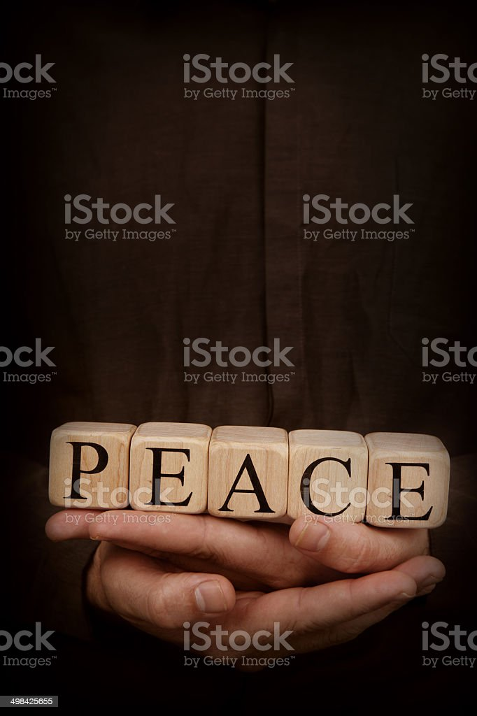 Peace - Toy Blocks in Hands on Dark Background royalty-free stock photo