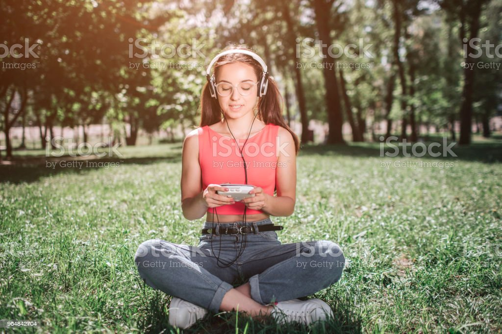 Peaceful and relaxed girl is sitting on grass with her legs crossed and listening to music. She has headphones on her ears. Girl is looking to music player and smiling royalty-free stock photo