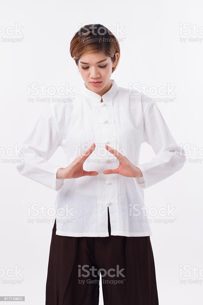 peaceful asian woman practice kungfu qigong, solar plexus concentration stock photo
