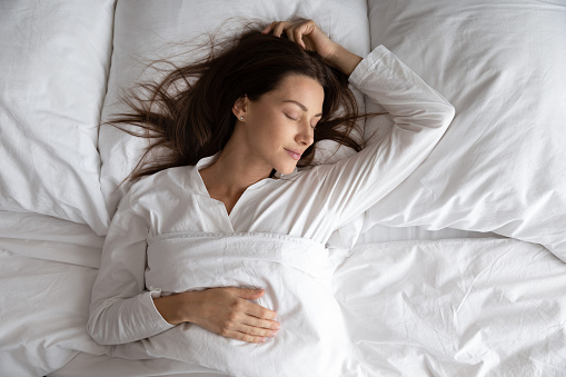Peaceful serene beautiful young lady wear pajamas lying asleep relaxing sleeping in cozy white bed on soft pillow resting covered with blanket enjoying good healthy sleep concept, above top view