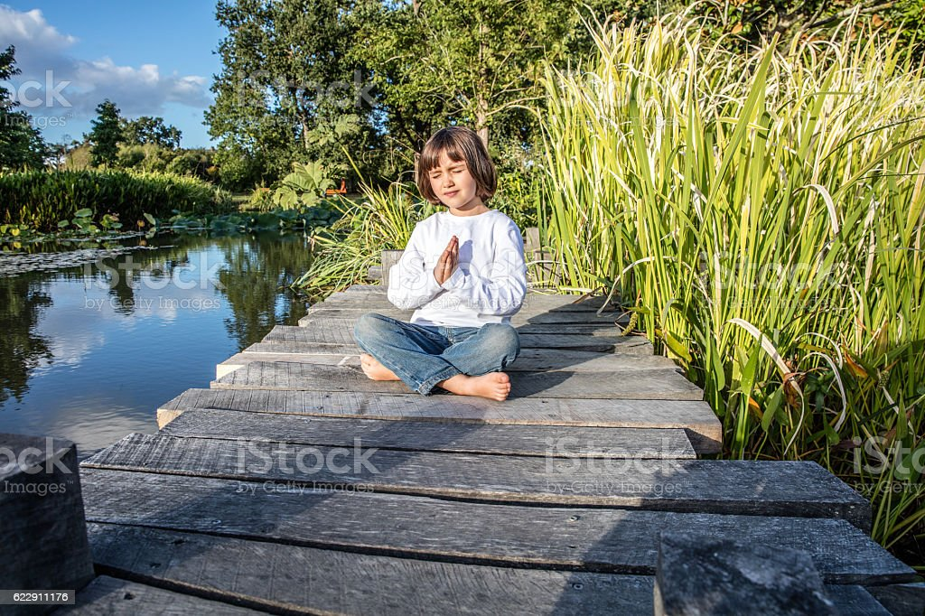 peaceful beautiful yoga child with bare feet near quiet water stok fotoğrafı