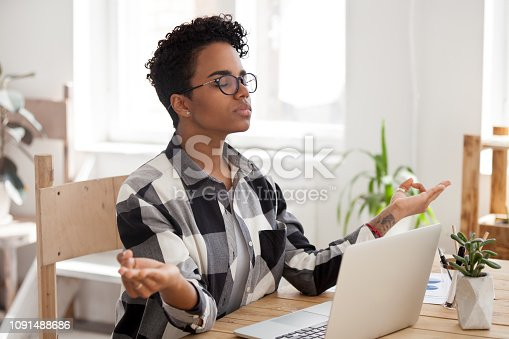 916520034istockphoto Peaceful black girl practice yoga at workplace 1091488686