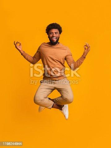 Peaceful afro man meditating with zen gesture in air over orange studio background