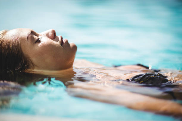 Peaceful blonde floating in the pool stock photo