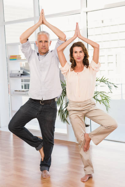 Peaceful casual business colleagues doing yoga stock photo