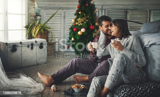 Closeup of a mid 20's couple having some coffee and relaxing by a window on a Christmas morning. They are laughing and captured in a very spontaneous moment.