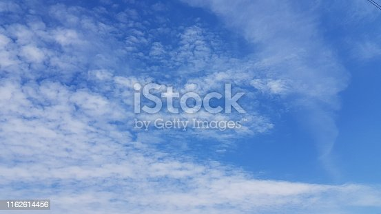 istock Peaceful cloudscape with light flying transparent clouds on bright blue sky background. High sky scenery with white spindrift clouds. Sunny day weather. Purity concept. 1162614456