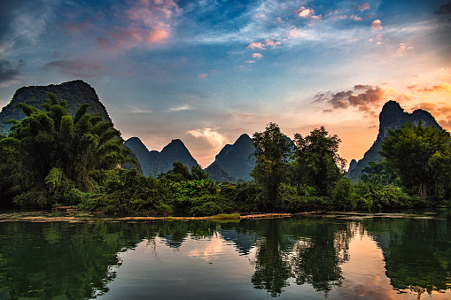 The hills and forests around Yangshuo reflected in the river during the twilight.