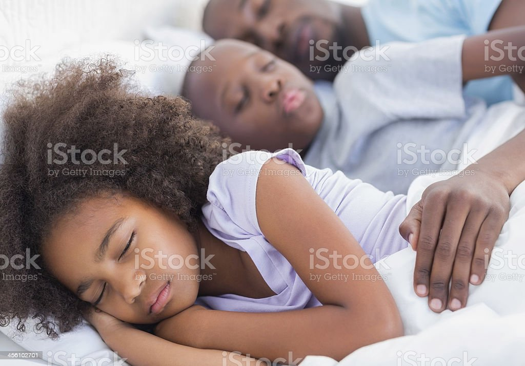 Peaceful father and children sleeping together in bed stock photo