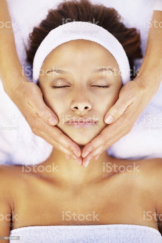 Peaceful female receiving a facial massage royalty-free stock photo