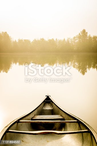 Peaceful fishing lake of Quebec in foggy morning with a canoe on the shore and the forest in background.
