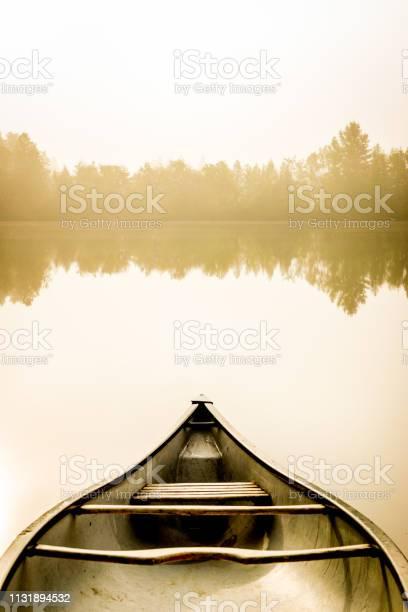 Photo of Peaceful fishing lake and canoe at sunrise.