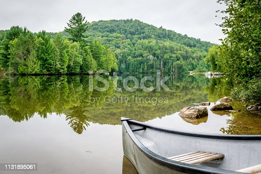 Peaceful fishing lake of Quebec with mountain range in background and canoe on the shore.