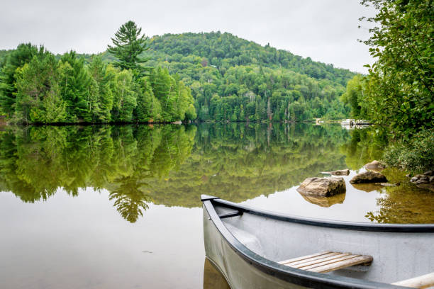 Peaceful fishing lake with mountain range Peaceful fishing lake of Quebec with mountain range in background and canoe on the shore. reflection lake stock pictures, royalty-free photos & images