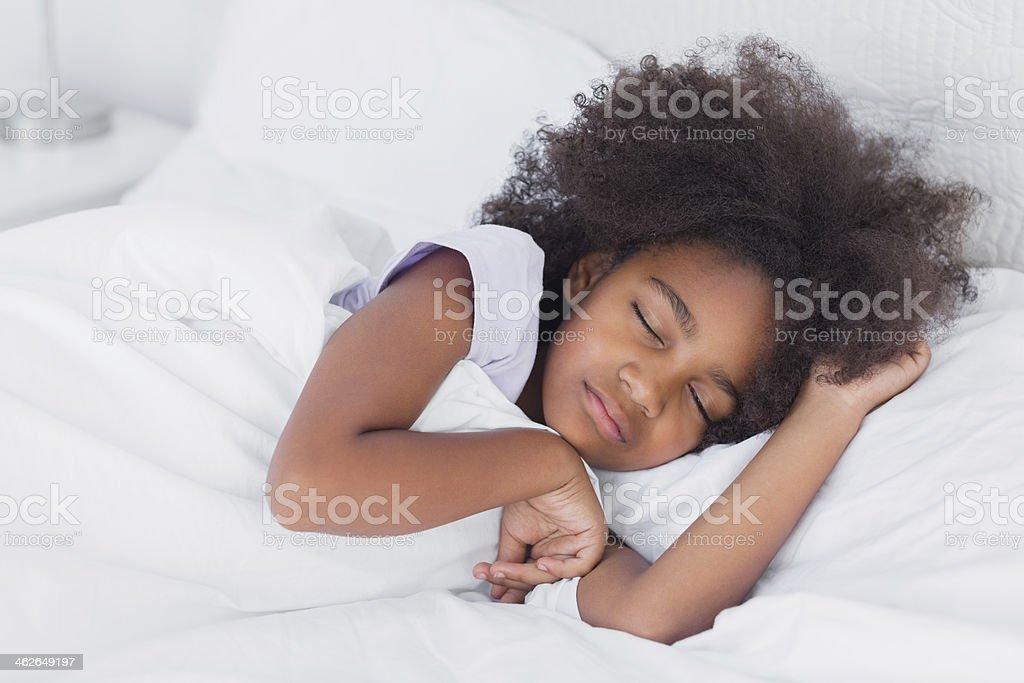 Peaceful little girl sleeping in bed stock photo