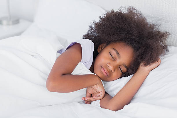 Peaceful little girl sleeping in bed stock photo