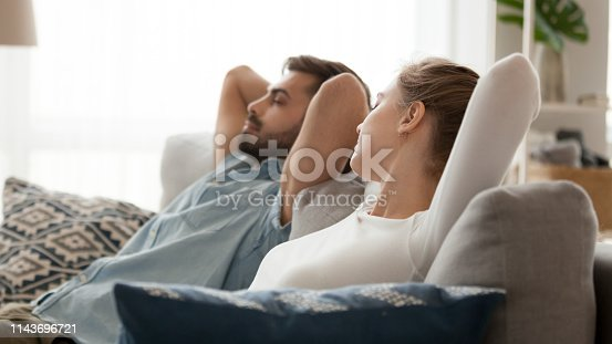 938682762istockphoto Peaceful man and woman relaxing leaning back on sofa 1143696721