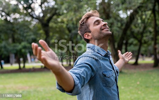Portrait of a peaceful man relaxing at the park with arms open and smiling - wellness concepts