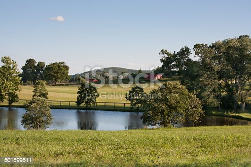 Charming country landscape of beautiful meadows with pond and red barns